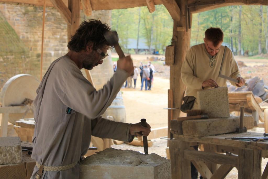 In der Bauhütte werden Steine zugeschlagen / Foto oben: Die Burgbaustelle (während der ausgiebigen französischen Mittagspause) / Fotos: Burgerbe.de