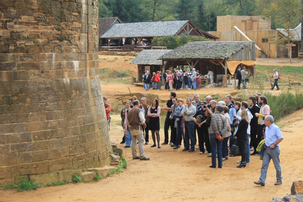 Eine Besuchergruppe bekommt Erklärungen am Fuß eines Burgturms. Dahinter eine der Bauhütten.