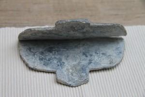 Kurioser Fund: Ein römisches Fluchtäfelchen aus Blei mit gut erkennbarem Münzabdruck