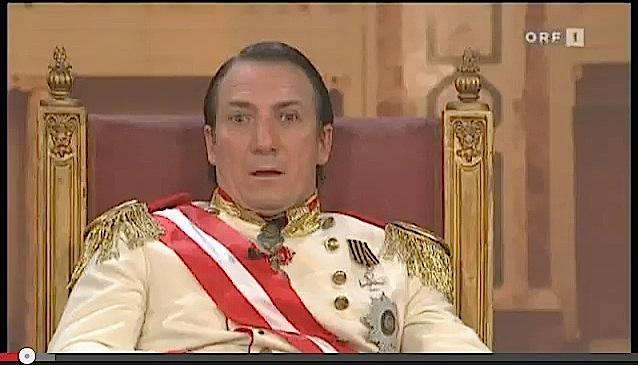 Robert Palfrader als Robert Heinrich I., Kaiser von Österreich, in der Wiener Hofburg / Bild: Screenshot Youtube