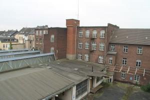 Innenhof der Samtweberei: rechts die Rückseite des Fabrikgebäudes. links die Dächer der Shed-Hallen