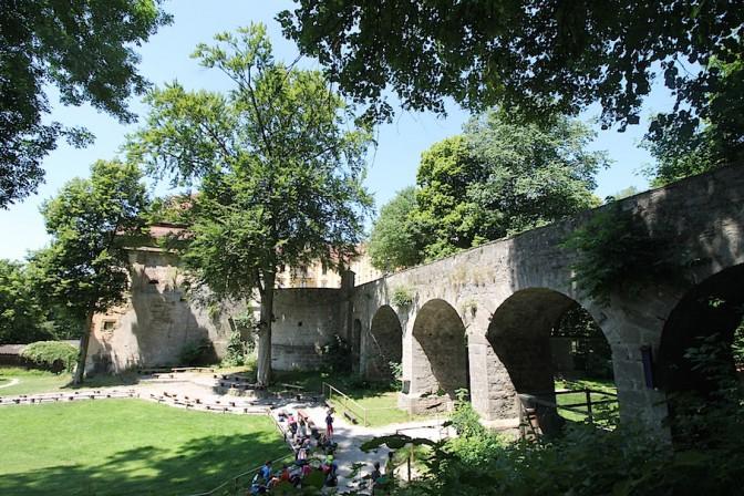 Eine mächtige Brücke führt zum Schloss. Auf der Wiese darunter zeigen die Falken, was sie können / Fotos: Burgerbe.de