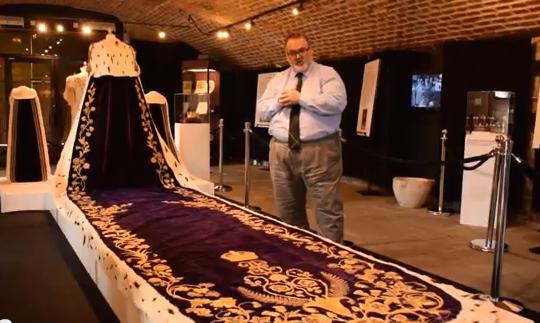 Ausstellungsmacher Thomas Baxter vor der royalen Schleppe / Bild: Screenshot Youtube