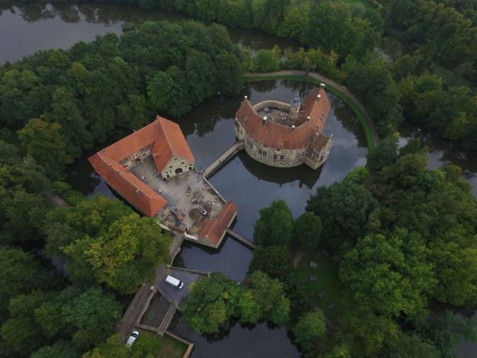 Die malerische Anlage von Burg Vischering aus der Luft. Im gemeinsamen Hausteich liegen links unten die Vorburg mit Bauhaus und Wirtschaftsgebäuden und oben rechts die Hauptburg. Foto: LWL/R. Klostermann